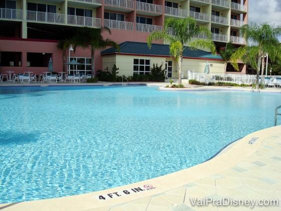 Foto da piscina do Blue Heron, com o prédio atrás e algumas palmeiras e cadeiras ao redor.