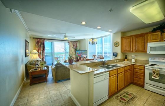 Foto da sala e cozinha completas no Blue Heron, com armários em madeira, um fogão, sofás e mesa de centro e janelas amplas.