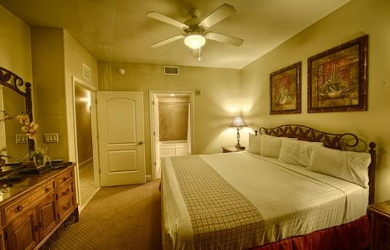 Foto do quarto de casal no Blue Heron, com uma cama de casal, penteadeira em frente e alguns quadros na parede.