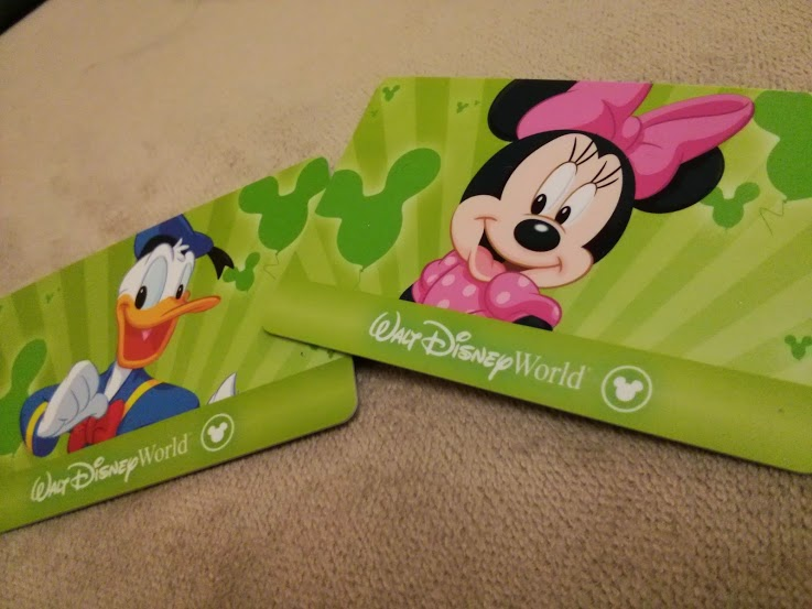 Foto dos cartões magnéticos verdes que são os ingressos da Disney, um com o Donald e outro com a Minnie. Eles tiveram um aumento de preços recente