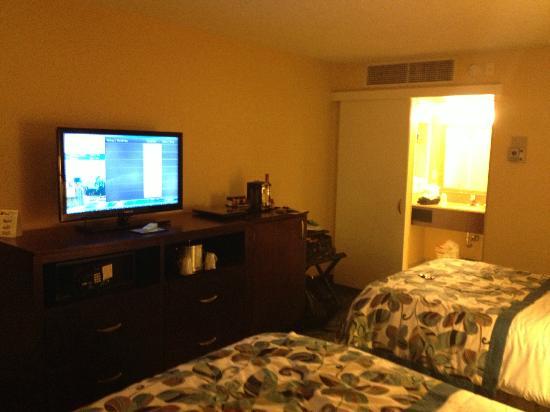 Outro ângulo do quarto do Wyndham, mostrando a TV em frente às camas e o banheiro ao lado