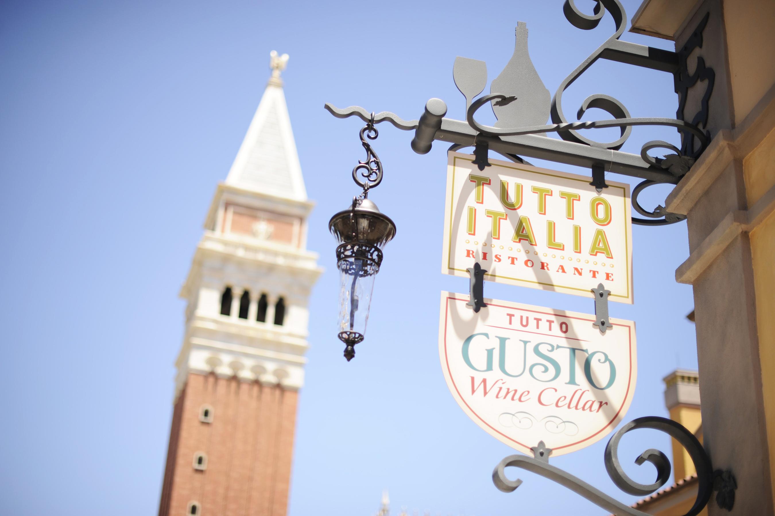 Foto da placa do Tutto Italia, com a torre do pavilhão da Itália no Epcot ao fundo e o céu azul