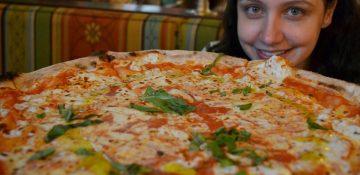 Foto da Renata sorrindo atrás de uma pizza gigante no Via Napoli, no Epcot