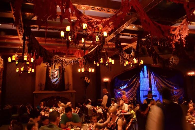 Um dos salões do Be Our Guest, nesse caso durante o jantar mas a decoração é a mesma em todas as refeições. Foto do interior do Be Our Guest mostrando a decoração com panos no teto.