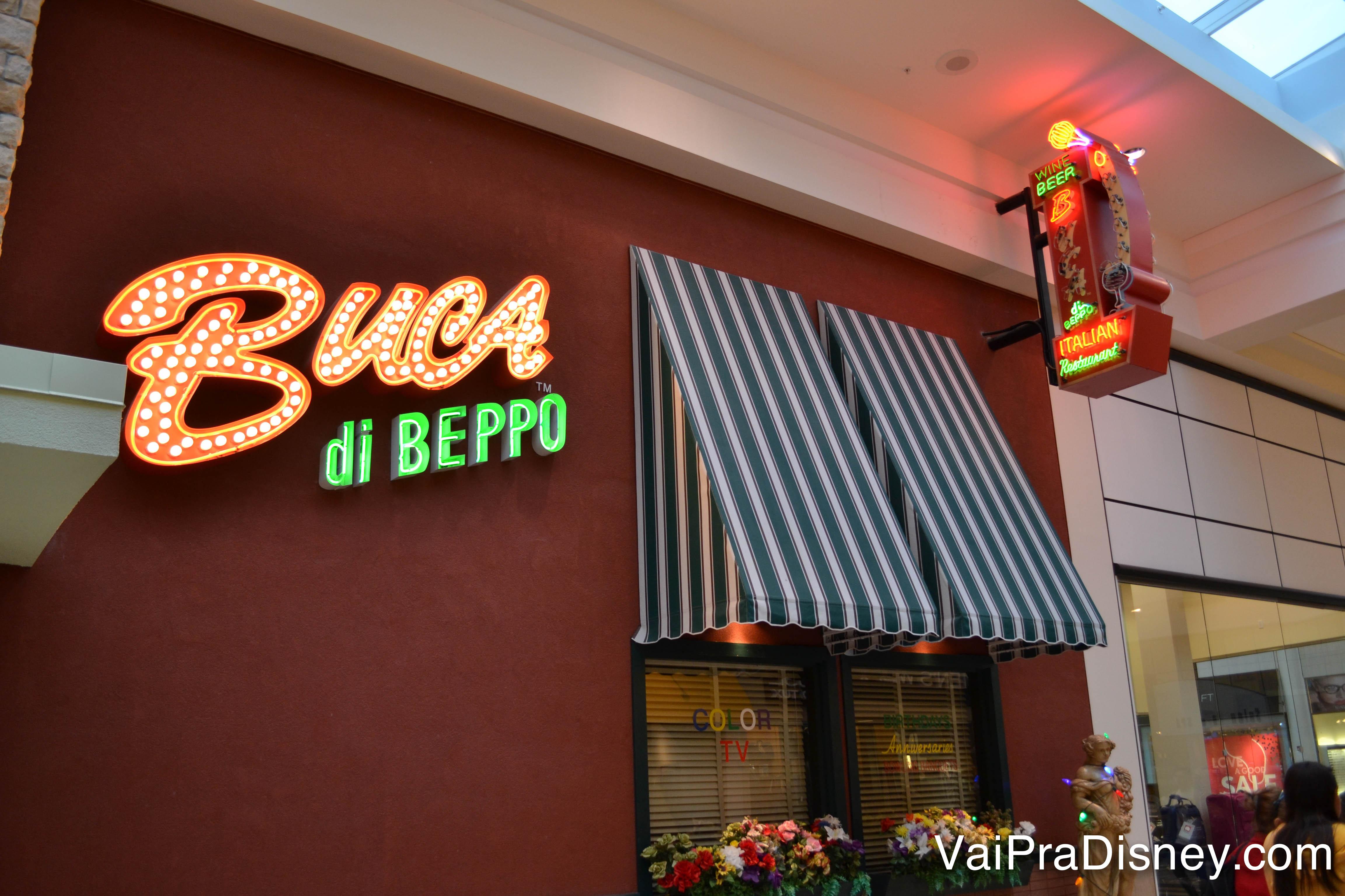 Foto da entrada do Buca di Beppo no Florida Mall, com o nome do restaurante em neon e toldos listrados em azul e branco