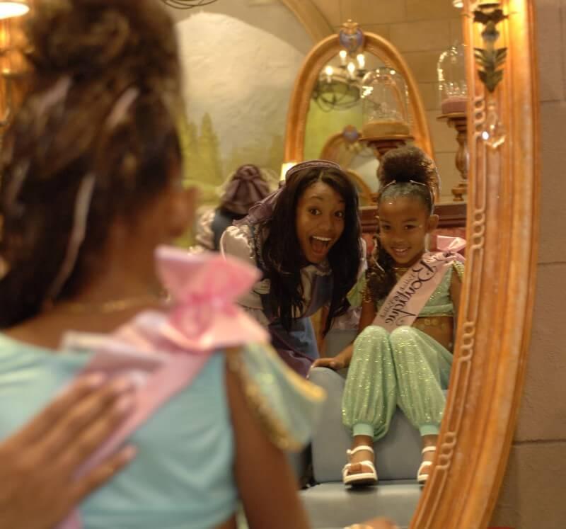 Momento mágico no Bibbidi Bobbidi Boutique: quando as meninas olham o próprio reflexo no espelho, já como princesas. Foto de uma menina se vendo no espelho, vestida de princesa, e sorrindo.