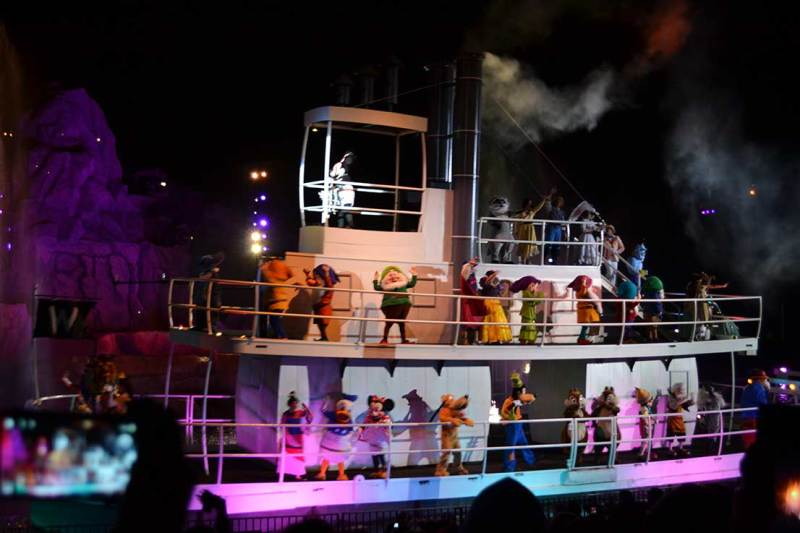 Foto do show Fantasmic no Hollywood Studios. A imagem mostra um barco no lago do parque, durante à noite, com muitos personagens dançando.