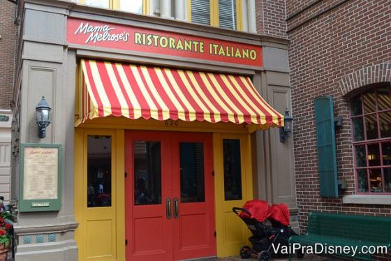 Foto da fachada do Mama Melrose's Ristorante Iitaliano. A porta é vermelha, a frente é pintada de amarelo, o toldo é listrado em vermelho e branco e a placa também é amarela e vermelha.