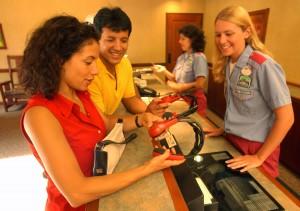 A imagem mostra duas pessoas retirando fones de tradução com funcionária da Disney