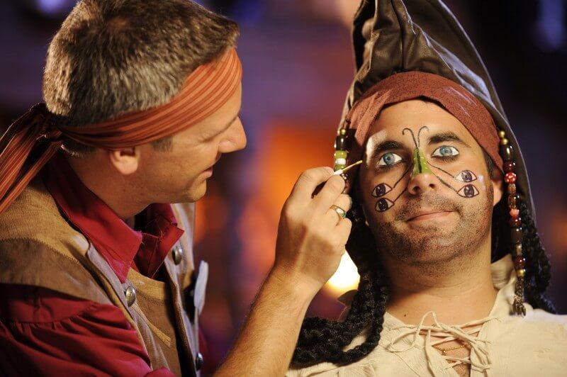 Lembra dessa maquiagem de pirata? Ela aparece em um dos filmes da série Piratas do Caribe. Foto de um adulto sendo maquiado por um funcionário da Disney no The Pirates League
