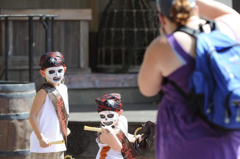 Vestidos de piratas, as crianças entram no papel durante todo o dia de parque! Foto de duas crianças vestidas de pirata no The Pirates League, com uma pessoa tirando foto deles
