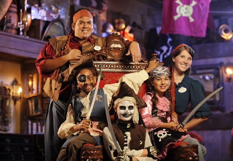 Foto de diversas crianças vestidas de pirata no The Pirates League ao lado dos funcionários da Disney.