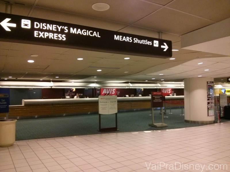 Placas no primeiro andar do aeroporto que indicam onde pegar o transporte da Disney em Orlando