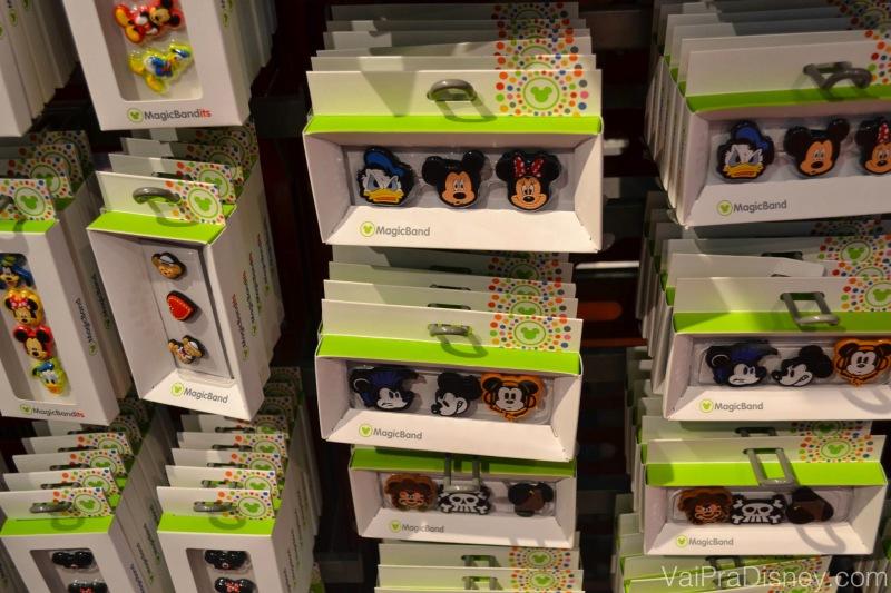 Acessórios para quem quiser enfeitar a sua MagicBand. Foto dos acessórios para colocar na MagicBand que são as carinhas de personagens como Mickey, Minnie e Donald, à venda em uma loja