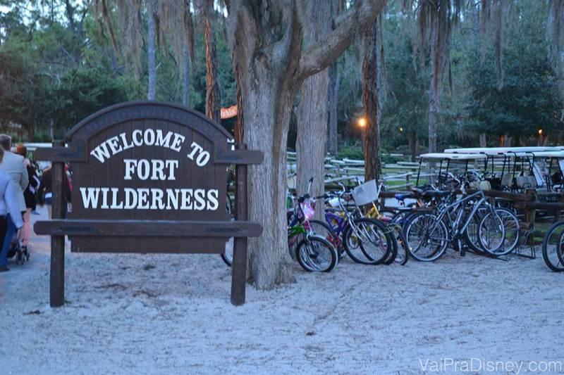 """Foto da placa que diz """"Welcome to Fort Wilderness"""" no hotel, com árvores ao fundo e bicicletas para alugar ao lado"""