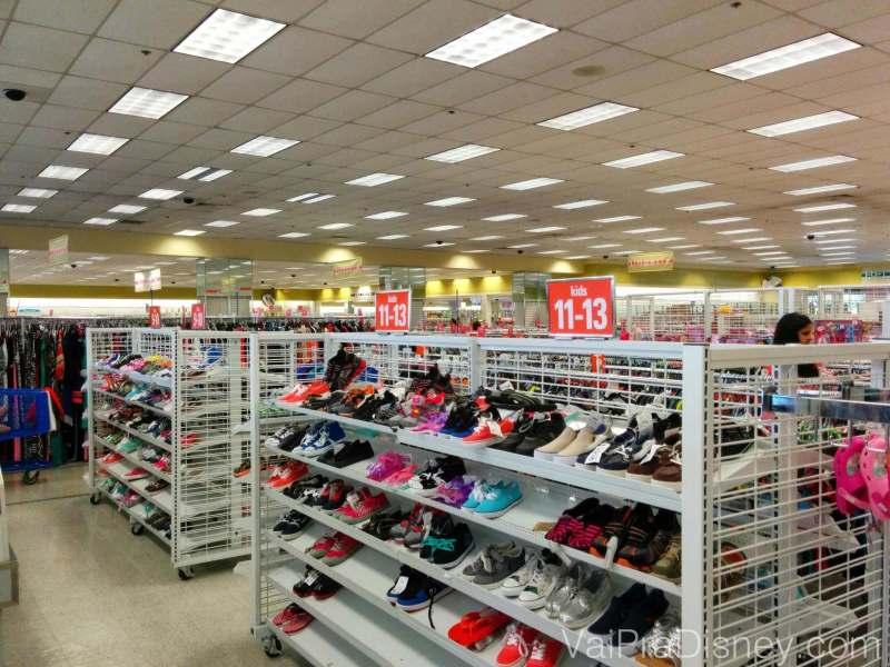 Calçados de crianças e ao fundo a imensa loja Ross. Foto de diversas prateleiras com sapatos infantis à venda na Ross.