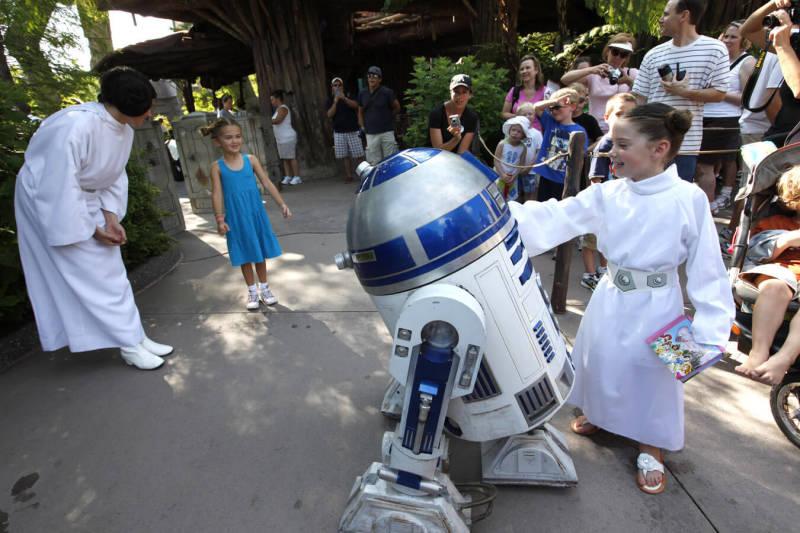 Famoso robozinho R2D2 tirando foto e brincando com uma criança fantasiada de princesa Léia