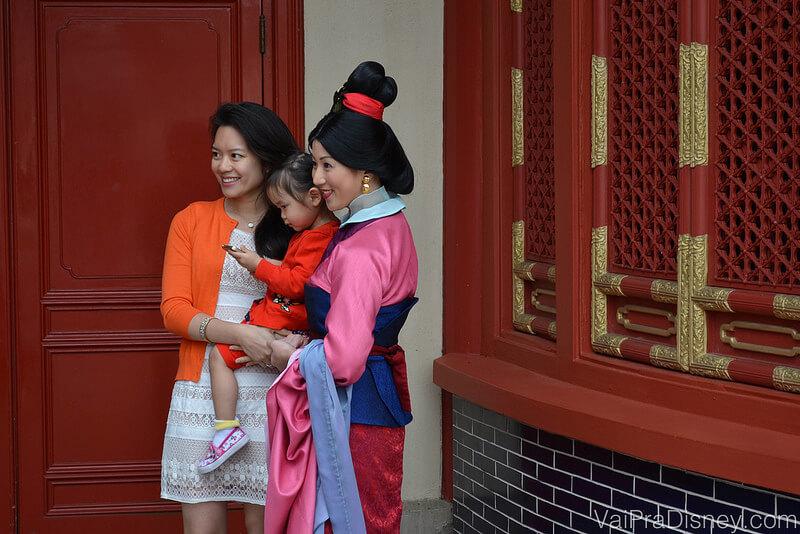Foto que eu tirei da Mulan, no pavilhão da China no Epcot, posando com uma família