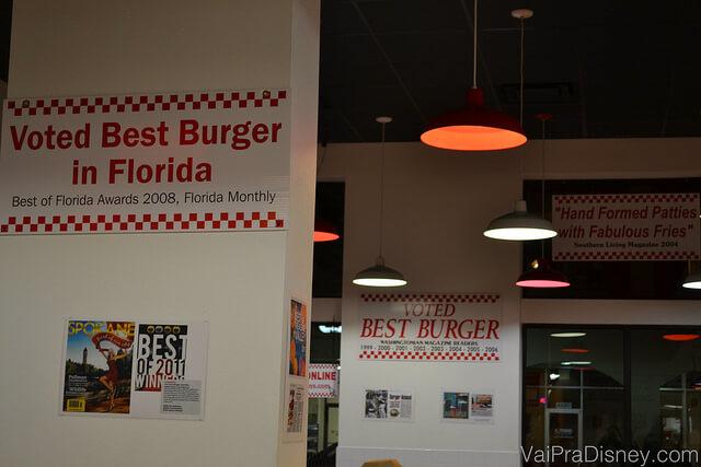 Várias placas com guias, jornais e revistas que recomendam o Five Guys no restaurante de Orlando
