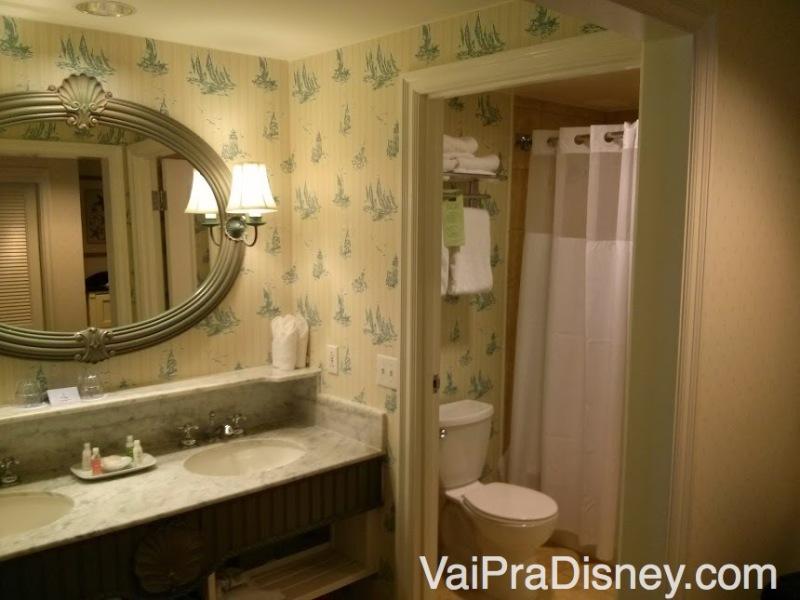 Banheiro e lavatórios separados, e alguns detalhes da decoração do Beach Club, com papel de parede claro e um espelho decorado com uma concha em cima