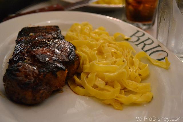 Prato com uma carne grelhada e macarrão acompanhando