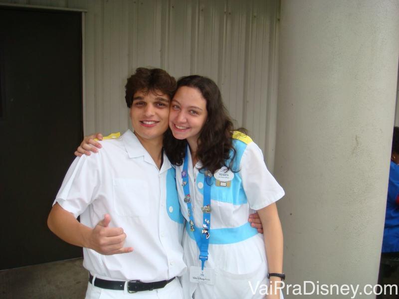 Foto da Re com seu amigo Bruno, numa foto de backstage. Ela está usando um colar azul com pins, que os funcionários trocam com os visitantes que querem colecionar