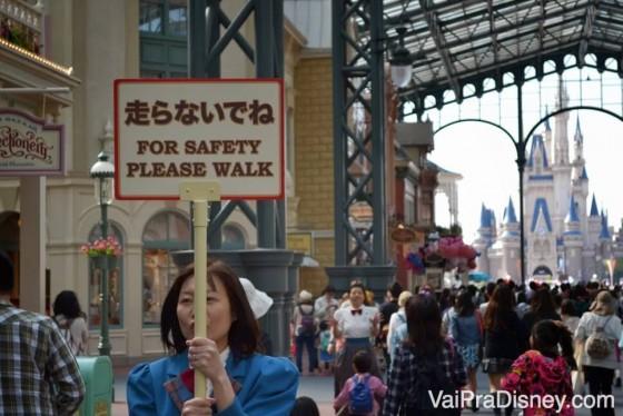 """Foto de uma funcionária segurando uma placa em japonês e inglês (""""for safety please walk"""") na Disney de Tóquio, com o castelo ao fundo e visitantes passando"""