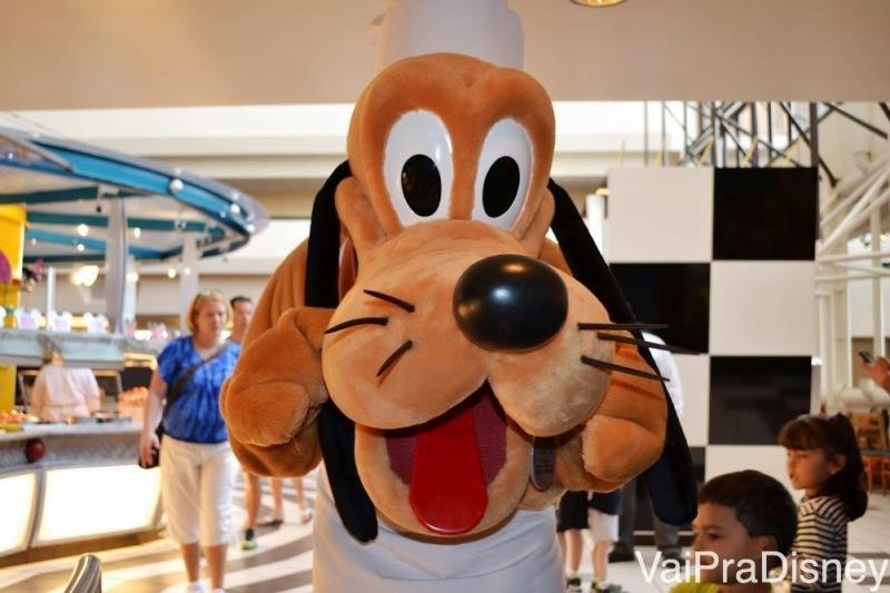 Foto do Pluto com roupa de chef posando para a câmera em uma refeição com personagens