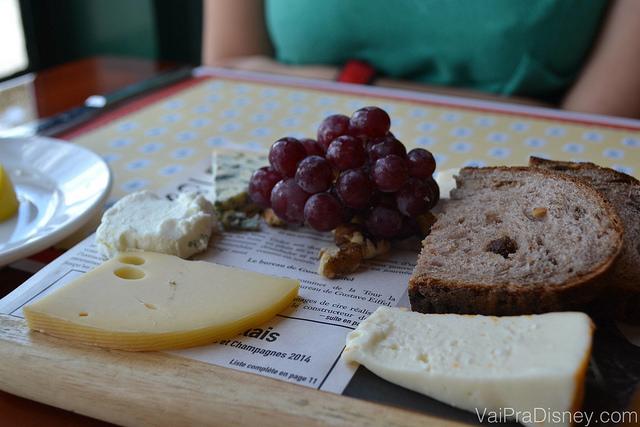 Foto da tábua de queijos do Chefs de France, acompanhada de uvas e pão.