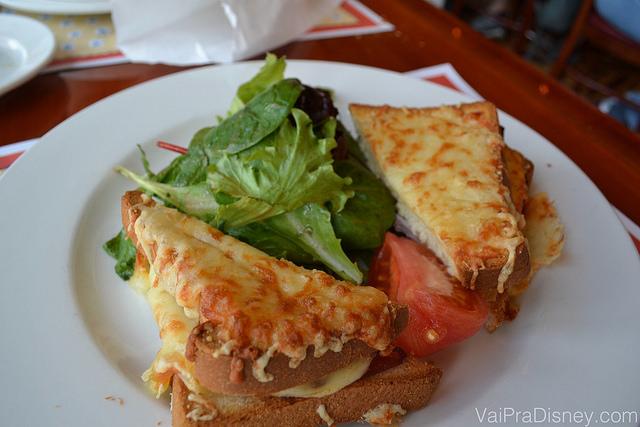 Imagem de um Croque Monsieur no prato, com queijo tostado cobrindo o pão e alface e tomate entre as duas fatias.