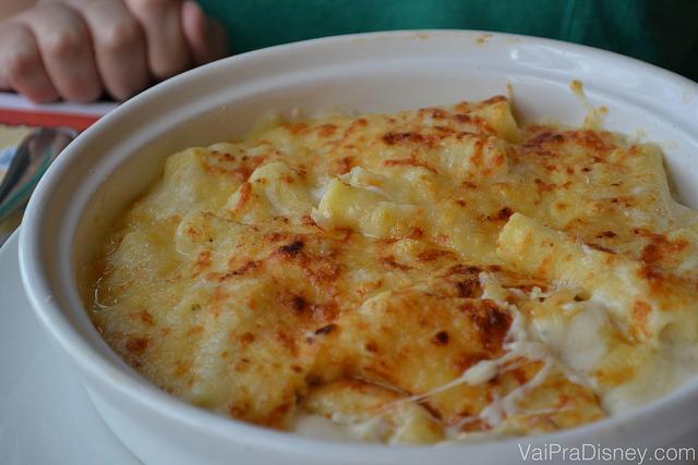 Imagem de um prato com uma massa coberta com molho branco e queijo gruyère gratinado.