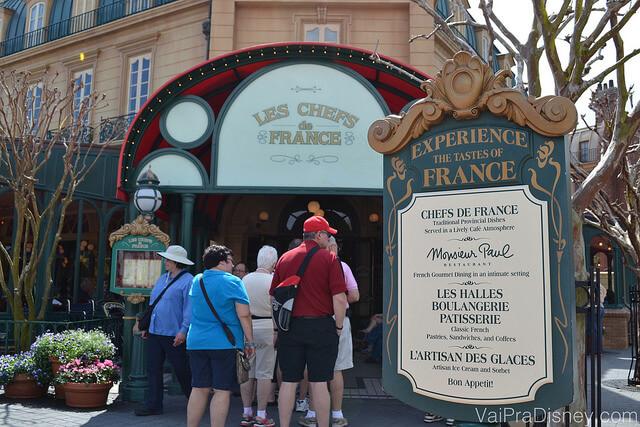 Imagem da fila na entrada do Chefs de France, com visitantes esperando para entrar ao lado da placa do restaurante.