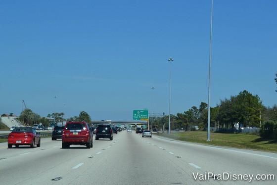 Dirigir em Orlando é tranquilo e mais gostoso do que dirigir no Brasil.  Foto da rodovia em Orlando, com diversos carros e o céu bem azul ao fundo.