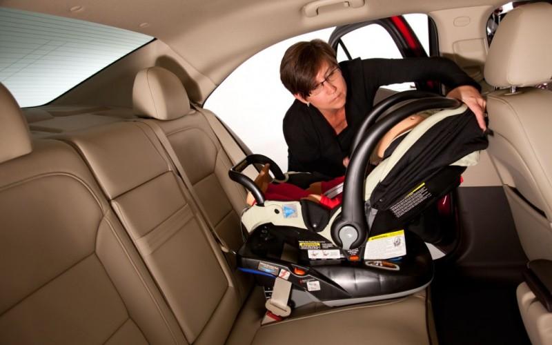 Cadeirinha para menores de 1 ano deve ficar virada para a traseira do carro. Foto divulgação Vernon Autogroup. Foto de uma mulher ajustando uma cadeirinha de bebê no banco de trás de um carro.
