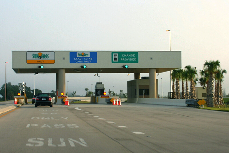 Veja os 3 tipos de cobrança em pedágios de Orlando. Assim você consegue dirigir pelos EUA. Foto de uma estação de cobrança de pedágio na rodovia em Orlando,, com diversas placas e um carro passando