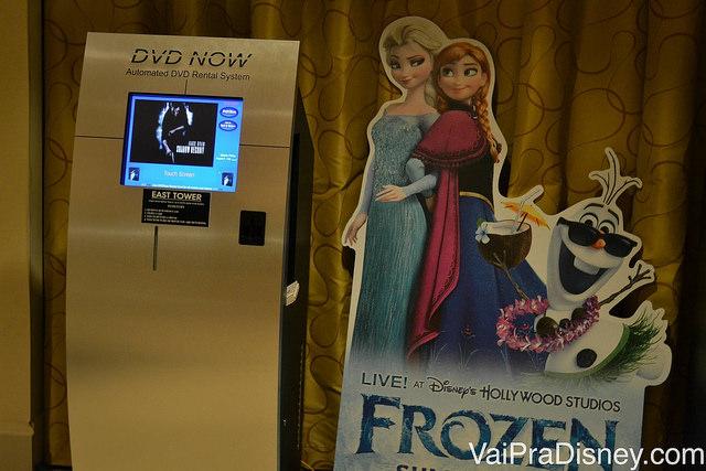Foto do totem de aluguel de DVDs, que já está incluído na diária, com um pôster de Frozen ao lado