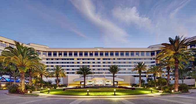 Foto da fachada do hotel Hilton Lake Buena Vista em Orlando, com palmeiras na frente e o céu azul atrás