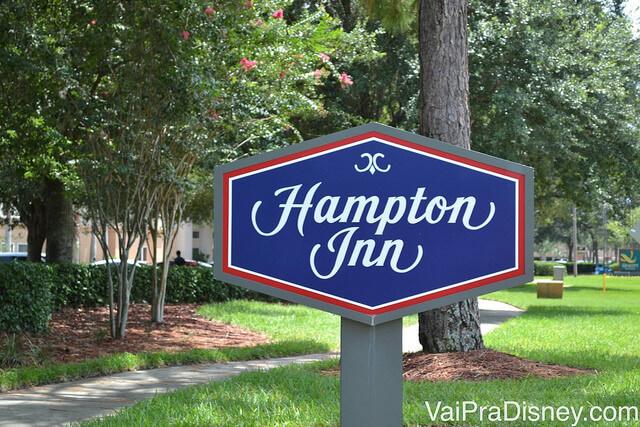 """Foto da placa do hotel Hampton Inn Lake Buena Vista, que tem """"Hampton Inn"""" escrito em branco sobre um fundo azul e bordas vermelhas"""