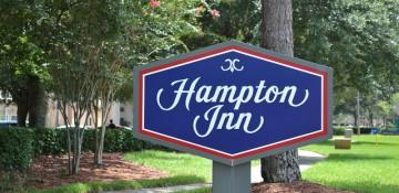 """Foto da placa do hotel Hampton Inn Lake Buena Vista, que tem """"Hampton Inn"""" escrito em branco sobre um fundo azul e bordas vermelhas."""