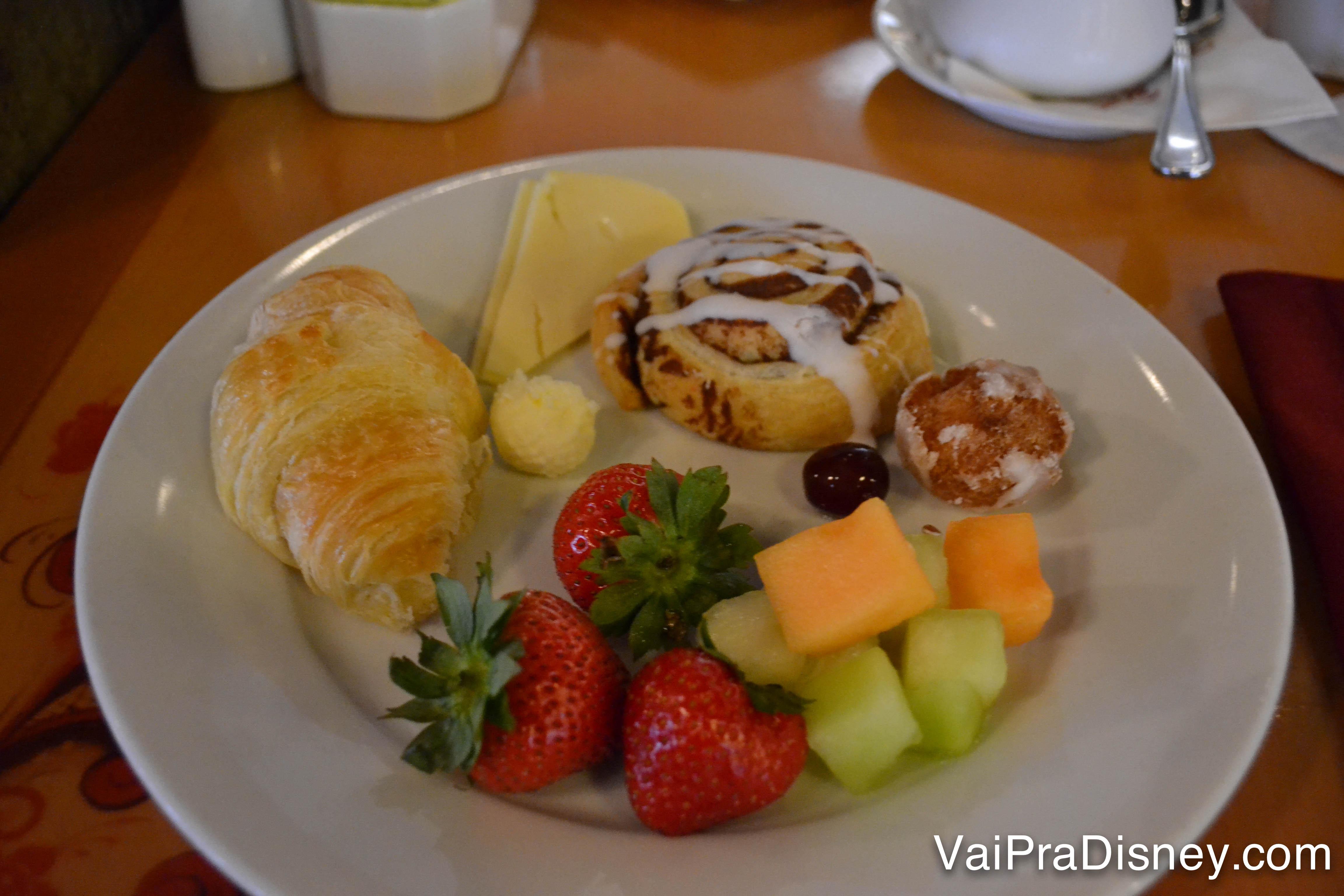 Foto do prato da Renata no café da manhã no Akershus, com croissant, pão doce, queijo e frutas