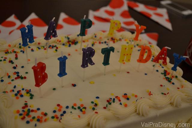 """Foto de um bolo de aniversário com velas soletrando """"Happy Birthday"""""""