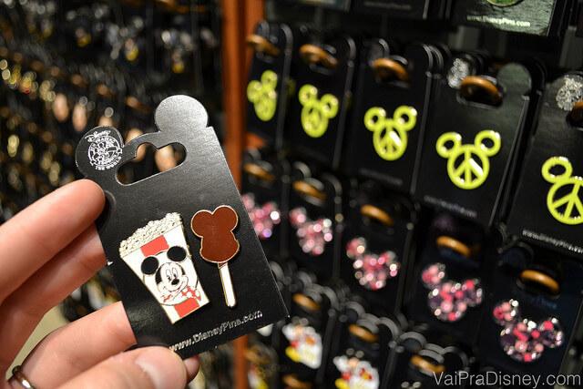 Foto dos pins menorzinhos que são vendidos em quase todas as lojas da Disney e existem milhares de modelos disponíveis, inclusive trazendo temas como aniversário e outras comemorações. Na foto, uma mão segurando um pin de pipoca e sorvete do Mickey.