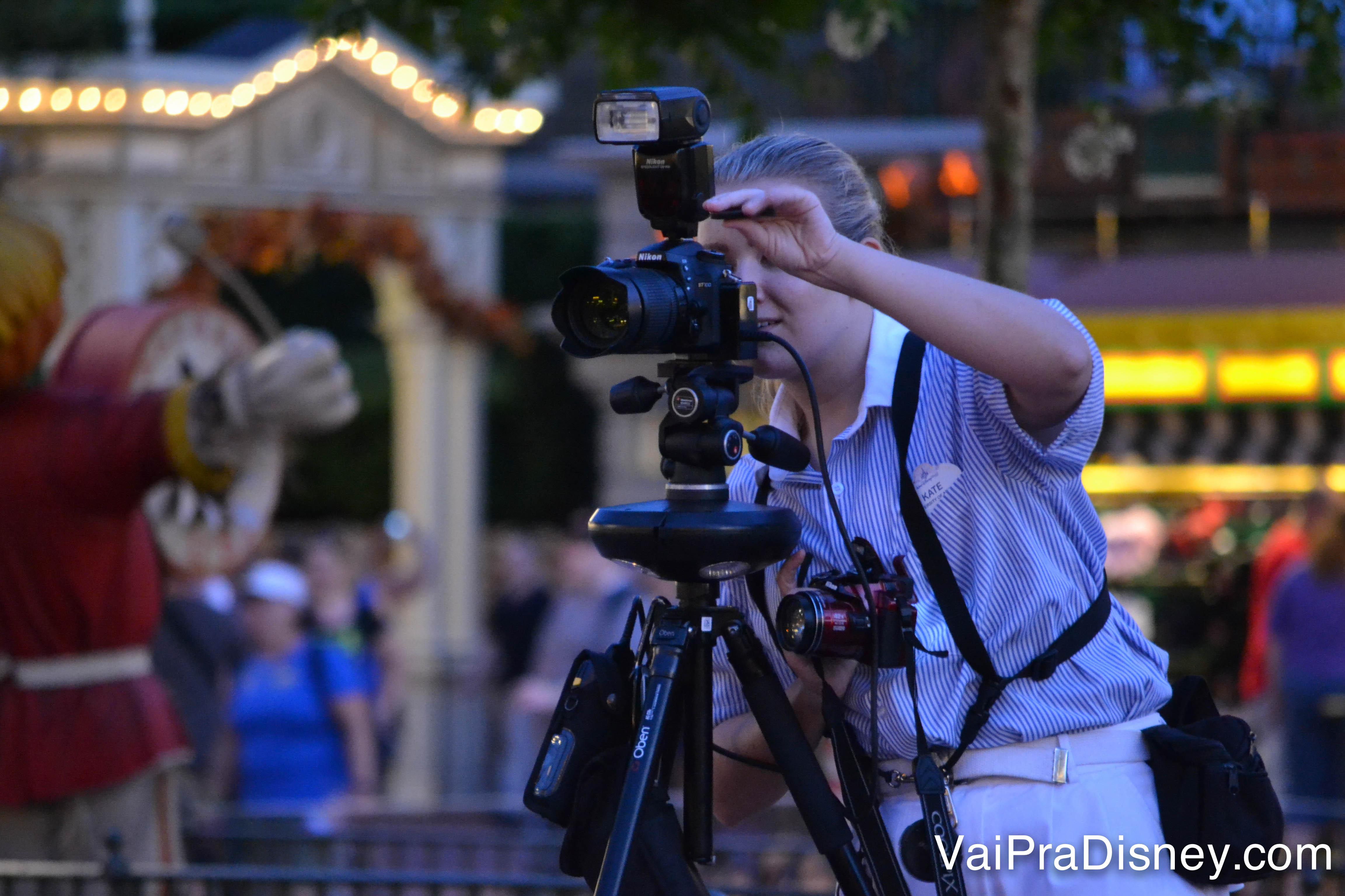 Esses são os fotógrafos do Photopass, é fácil de localizar com as câmeras e uniforme. Foto de um dos fotógrafos do Disney Photopass, atrás da câmera no parque enquanto fotografa um visitante.