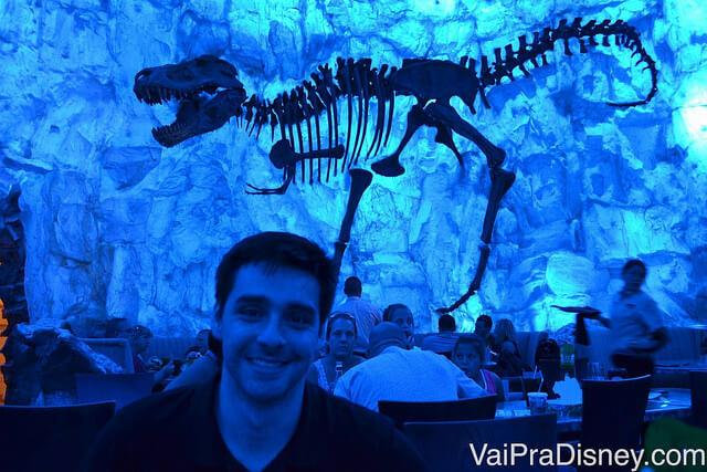 Foto do Felipe em uma iluminação azul, com um esqueleto de Tiranossauro Rex ao fundo na parede
