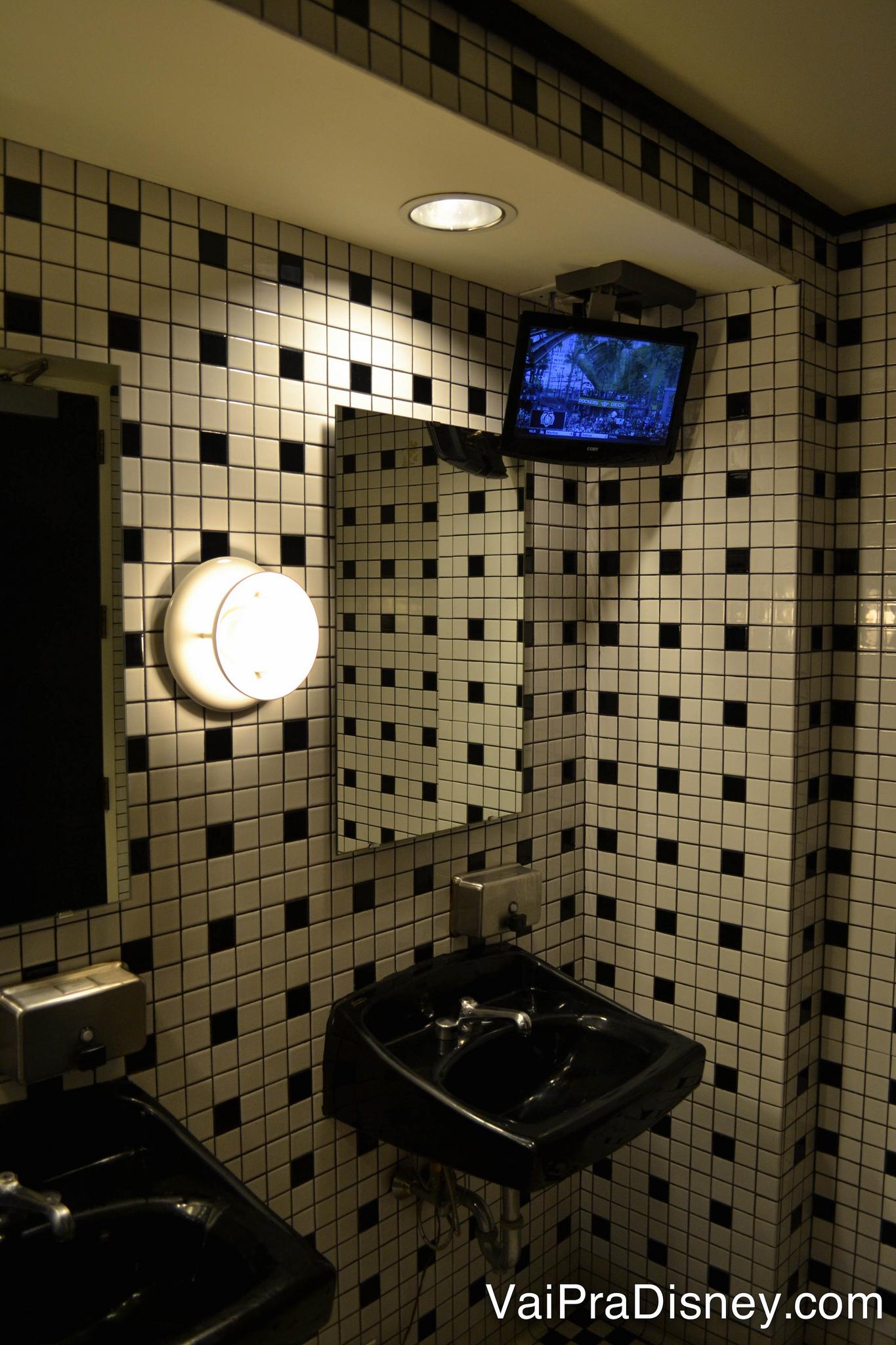 Pia no banheiro com uma TV, logo acima do espelho, no ESPN Club