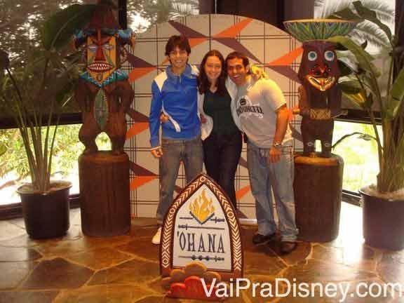 Foto da Renata com dois amigos na entrada do Ohana, toda com decoração havaiana