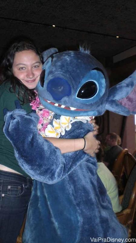 Foto da Renata abraçada no Stitch, com colar havaiano, no café do Ohana