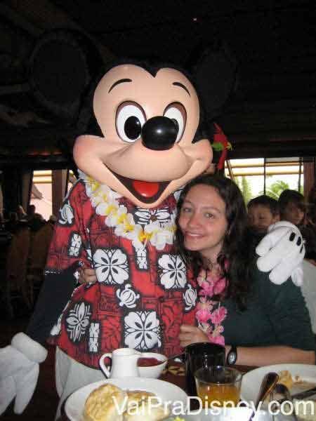 Foto da Renata abraçada com o Mickey havaiano (de camisa florida e colar) no Ohana