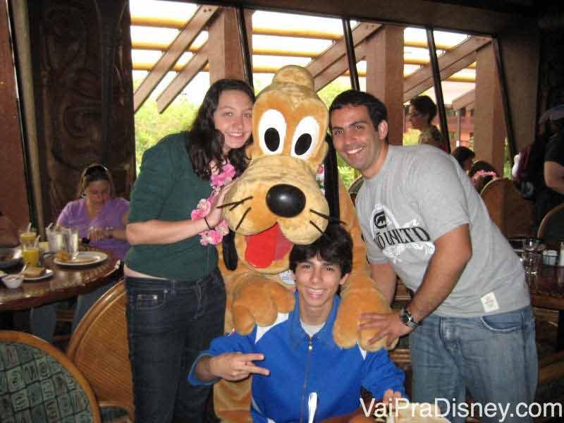 Foto da Renata de colar havaiano, com dois amigos e o Pluto, no café da manhã do Ohana