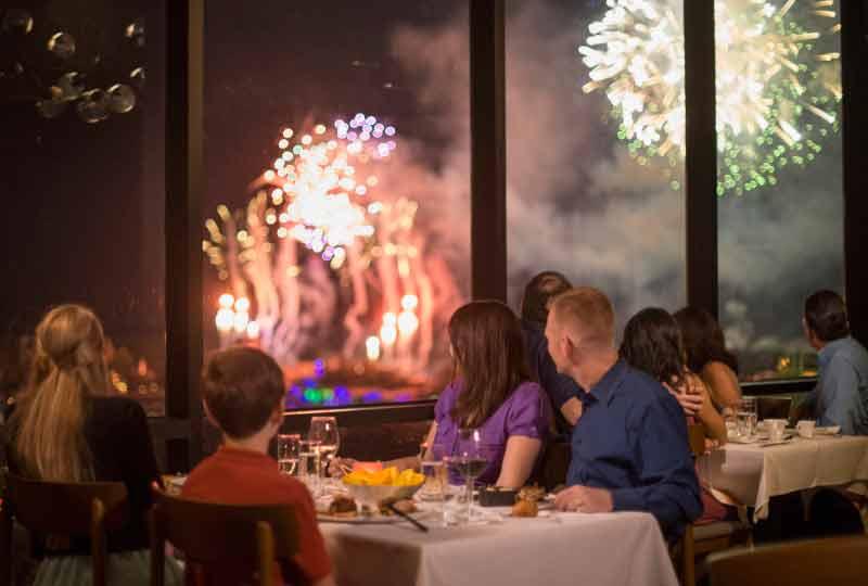 Jantar no California Grill, que fica no Contemporary Resort e oferece uma vista privilegiada dos fogos do Magic Kingdom. Foto de uma mesa com uma família vendo os fogos pela janela do restaurante California Grill, do Contemporary